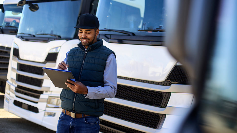 Man using an ELD in front of a truck fleet