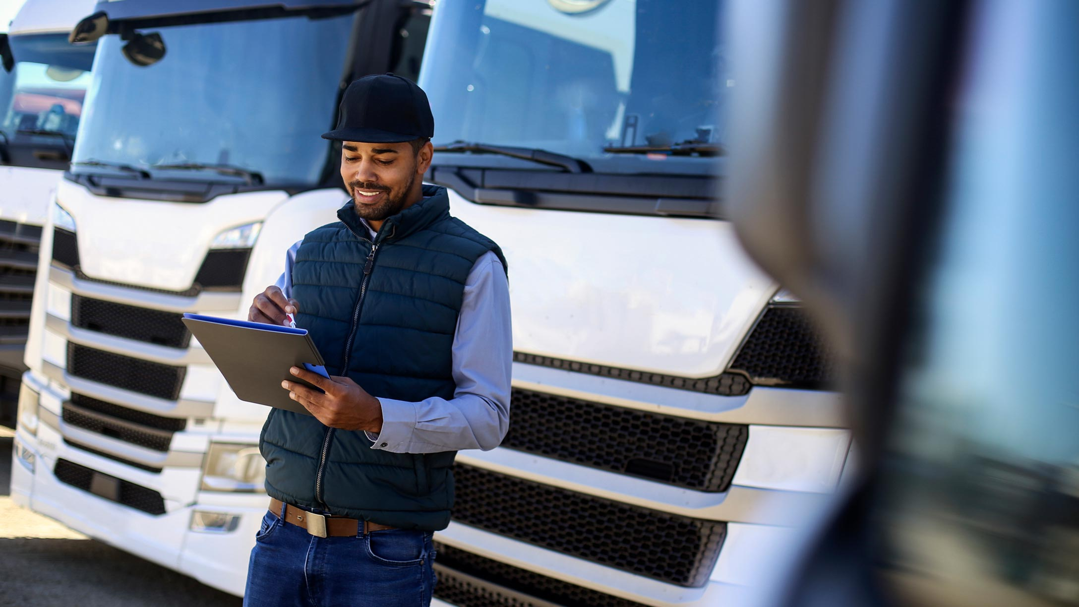Person standing in front of truck using tablet.