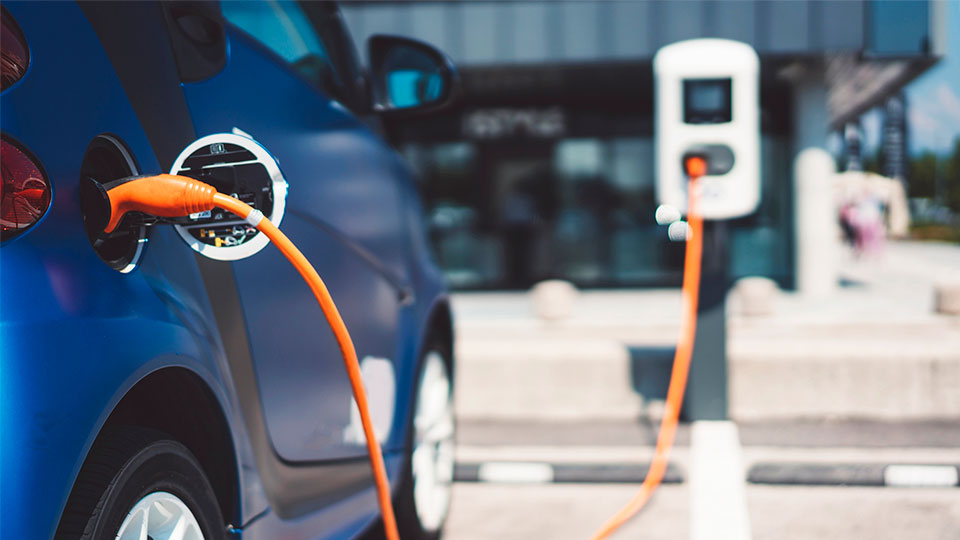 A blue electric vehicle charging with an orange cord