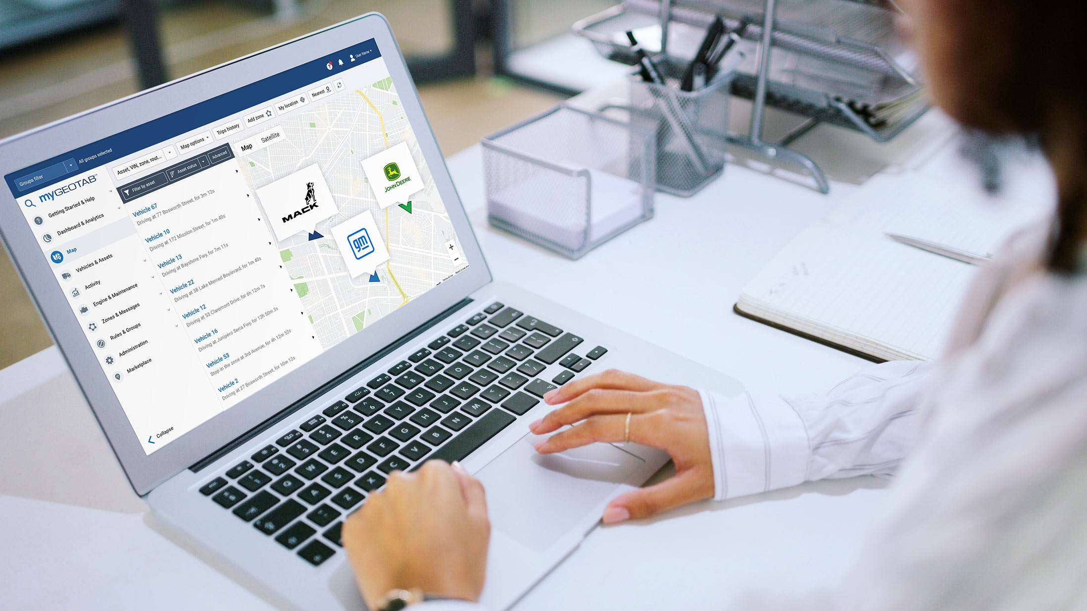 A woman looking at her computer screen which has MyGeotab