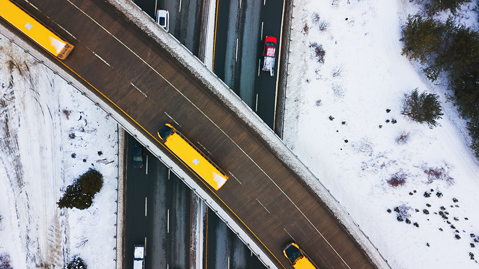 A fleet of trucks on the highway during winter