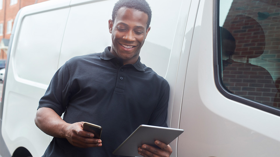 Person leaning against a vehicle looking at a tablet and phone