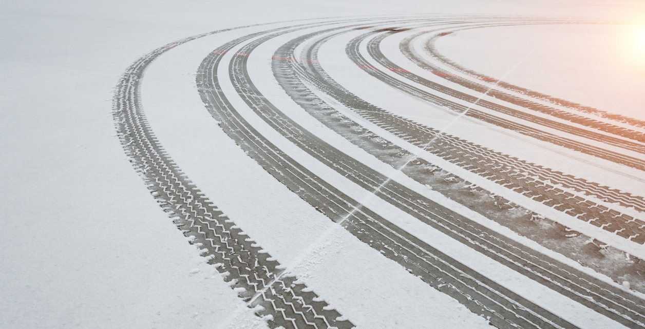 multiple sets of tire tracks in snow on a road