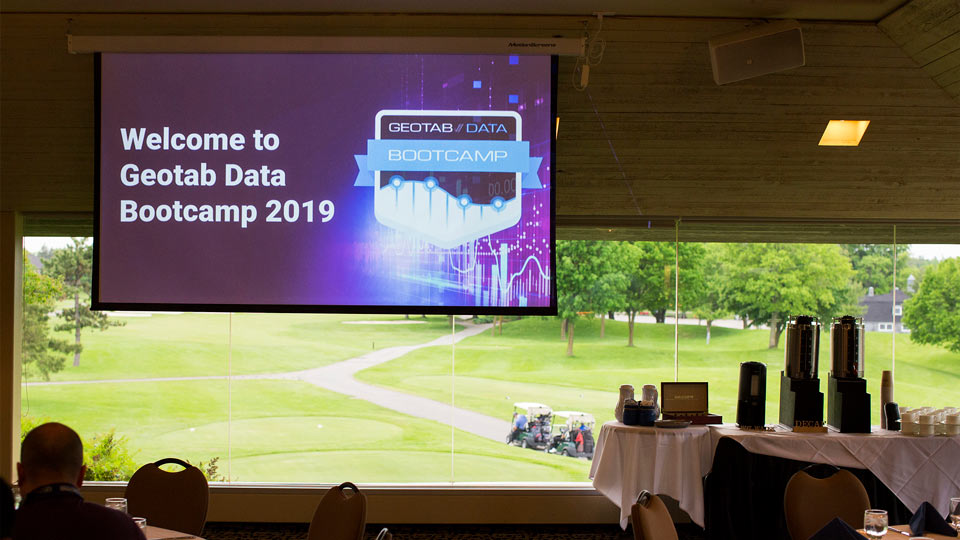 A screen in a conference room introducing Geotab Data Bootcamp 2019