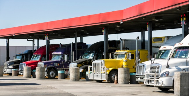 A row of semi trucks lined up at a fuel station