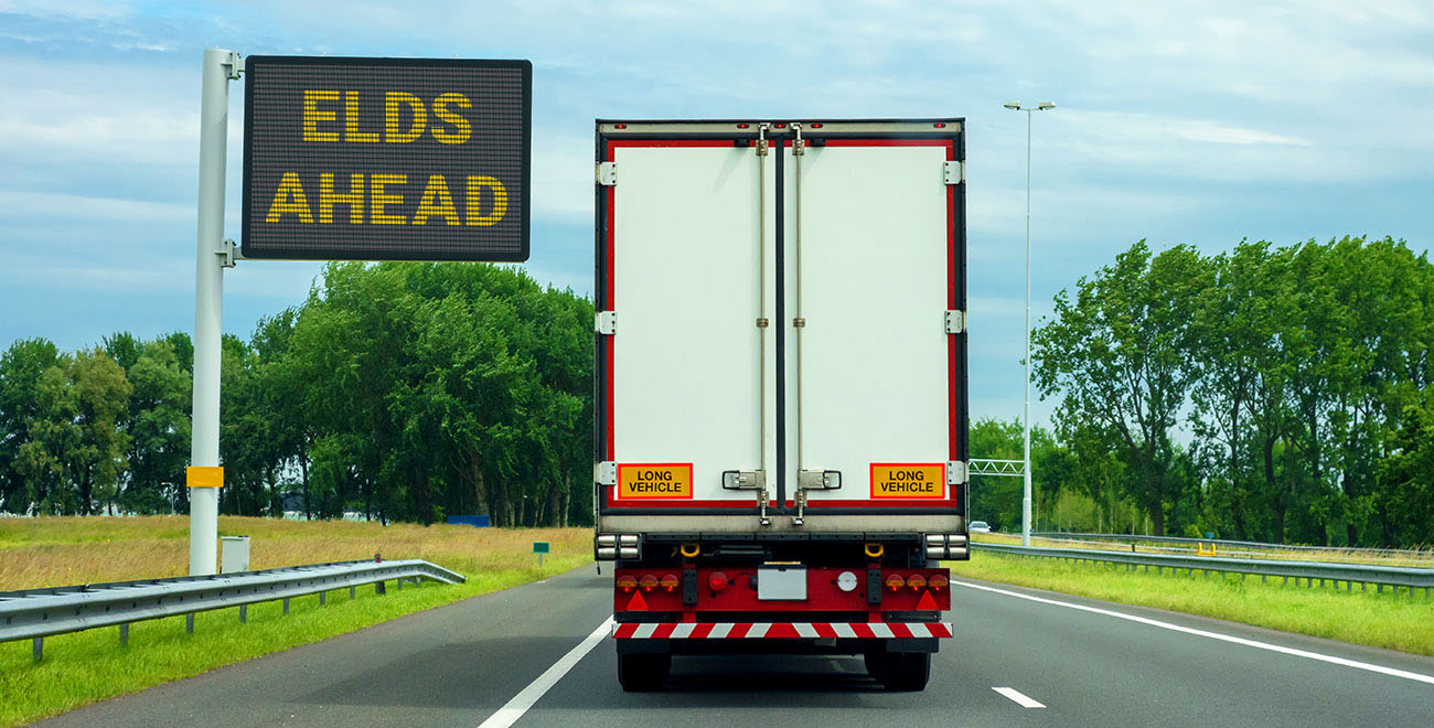 """Back of a white transport truck on a road with a road sign saying """"ELDS AHEAD"""""""