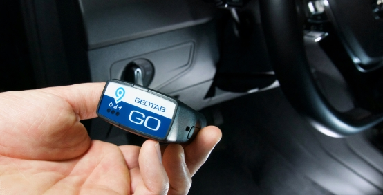 Hand holding Geotab GO device with vehicle dashboard in the background