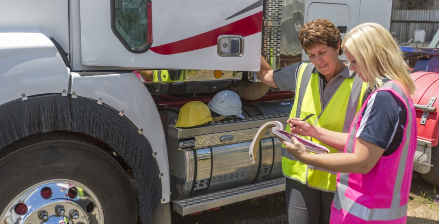 Two women standing outside a semi truck looking at a clipboard