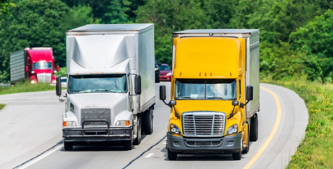 Two semi trucks driving side by side, one is white and one is yellow