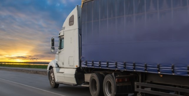 A semi truck driving at sunset