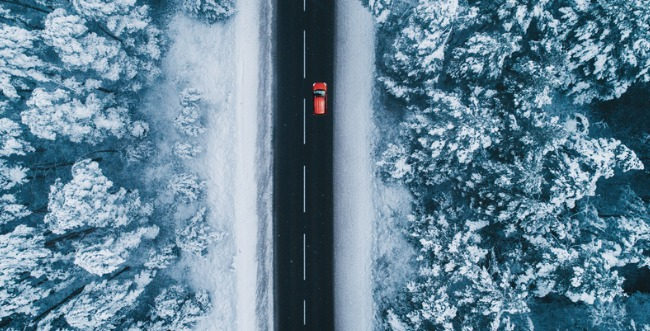 Top view of a car driving down a road in the winter