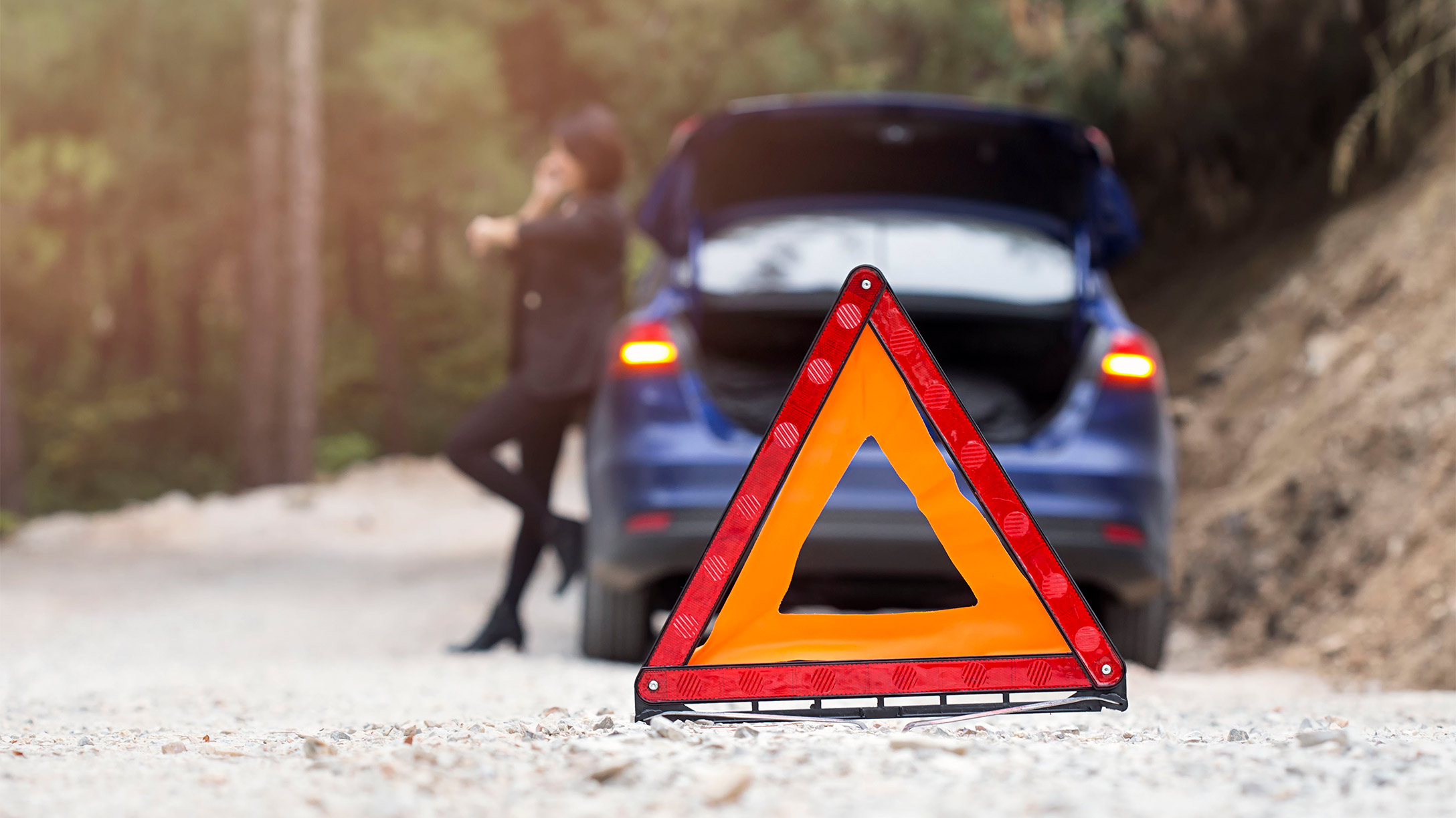 A woman standing against a broken down vehicle with a warning cone in the foreground