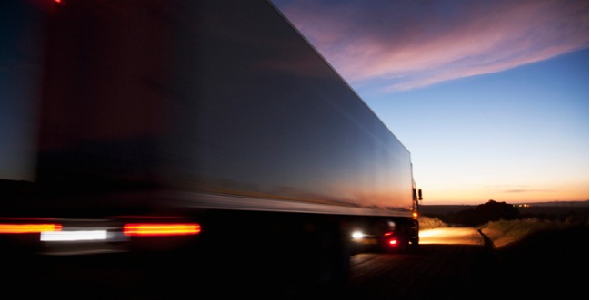 A semi truck driving at dusk