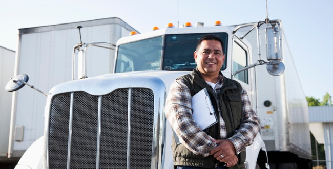 Man posing in front of semi truck with a clipboard tucked between his arm