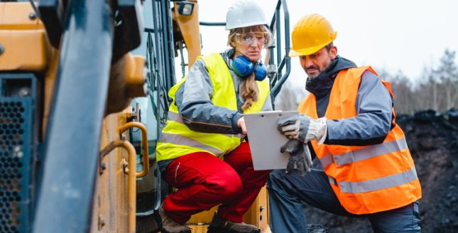 Two construction workers looking at a clipboard
