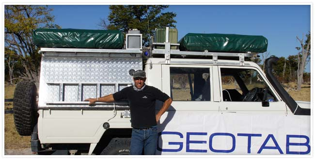 Man standing in front of a white vehicle with the a Geotab banner