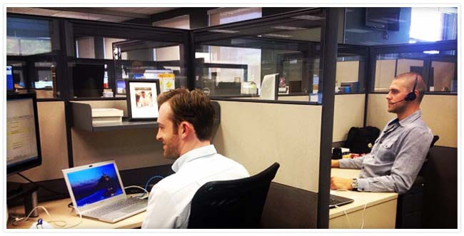 Two male employees sitting at their cubicles, one with a headset on and the other with a laptop open