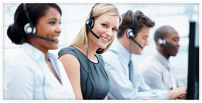 Four customer support employees wearing headsets sitting next to each other with one blonde employee smiling and looking at you.