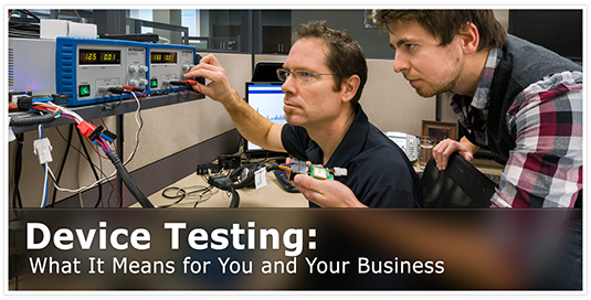 Two male employees at a desk with a unfinished GO device attached to wires for testing