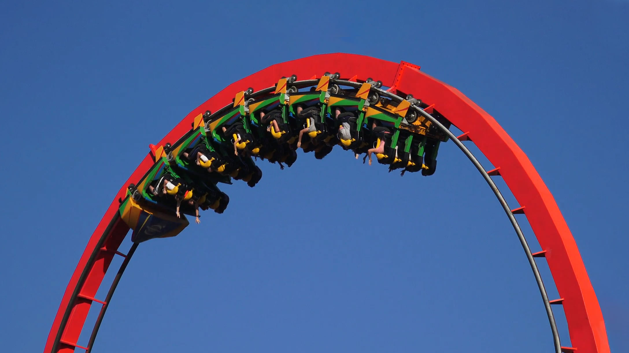A a red roller coaster with the cart going upside down using g-force.