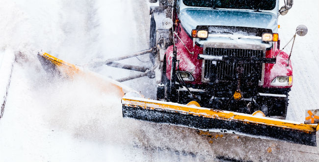 Image of a vehicle with a snow plow plowing snow