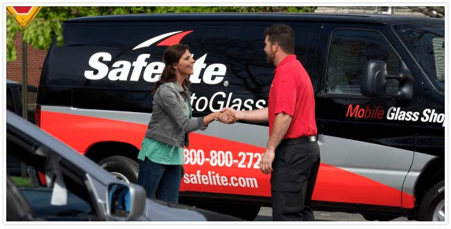 Employee wearing red shirt shaking female customers hand in front of company van.
