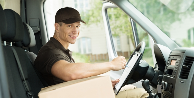 Delivery man with package sitting in a truck