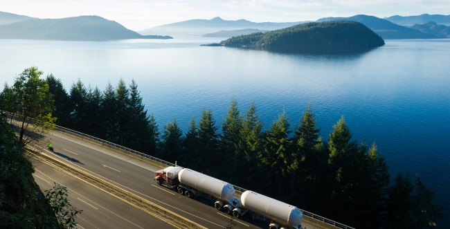 A tanker truck driving along a highway on the coast