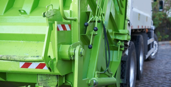 Back of a lime green garbage truck