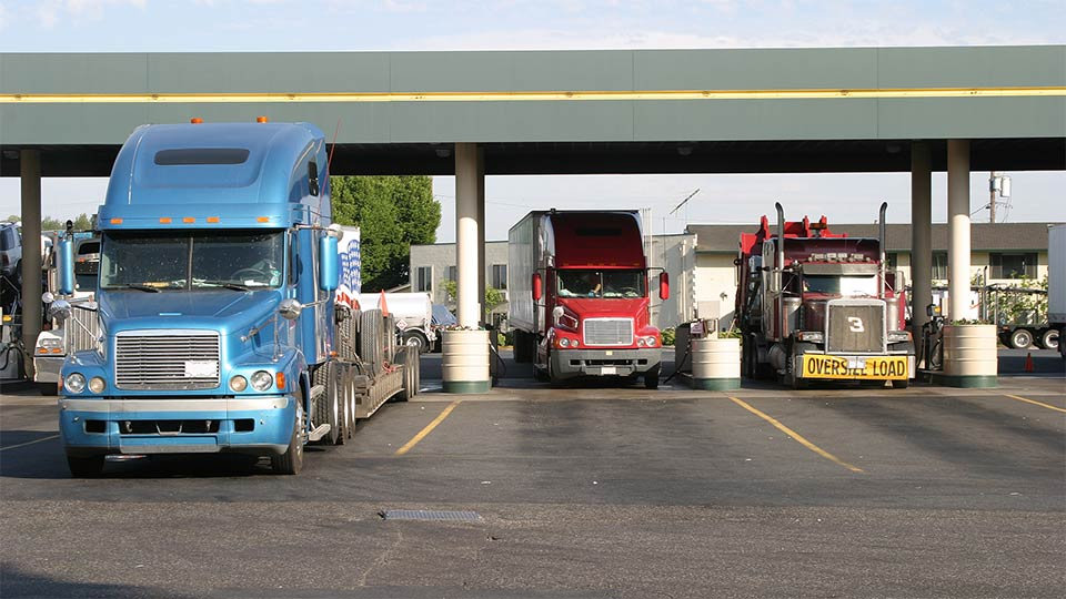Three semi trucks filling up at a gas station