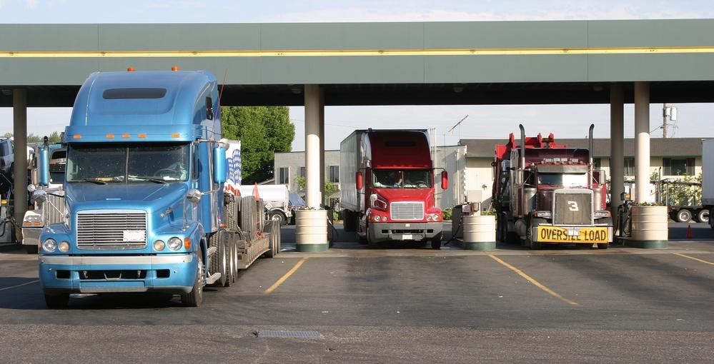 Three semi trucks filling up at a gas station