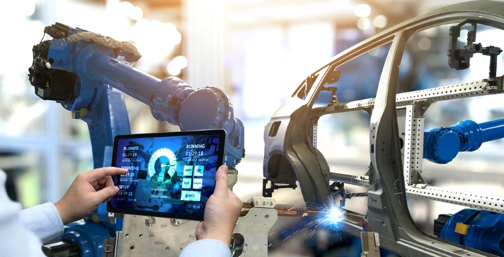 A person holding up a tablet at a car manufacturing plant