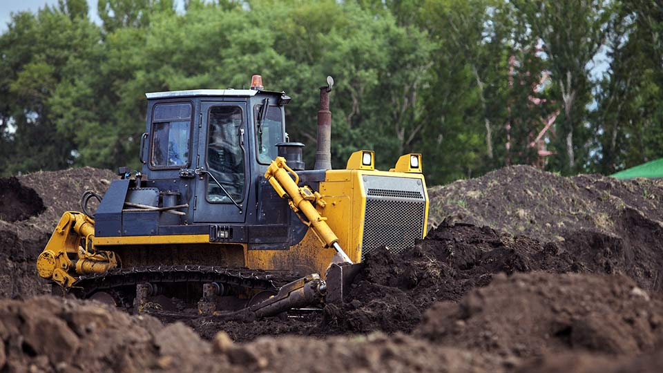 yellow excavator digging in dirt