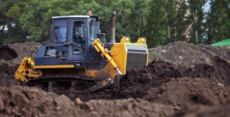 yellow excavator digging in dirt