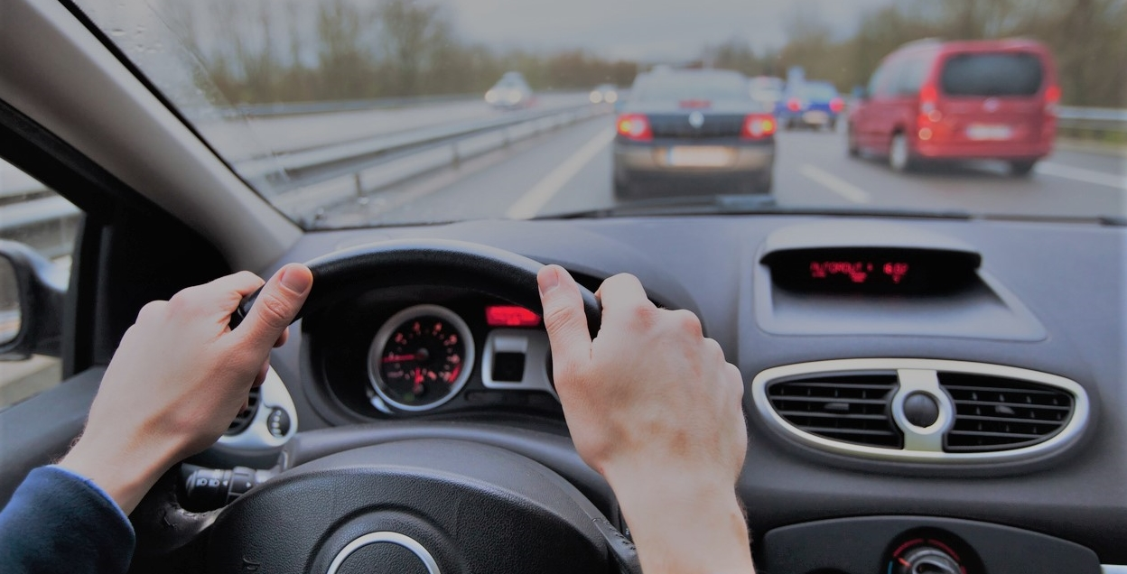Point of view of a person driving with two hands on the steering wheel on a highway