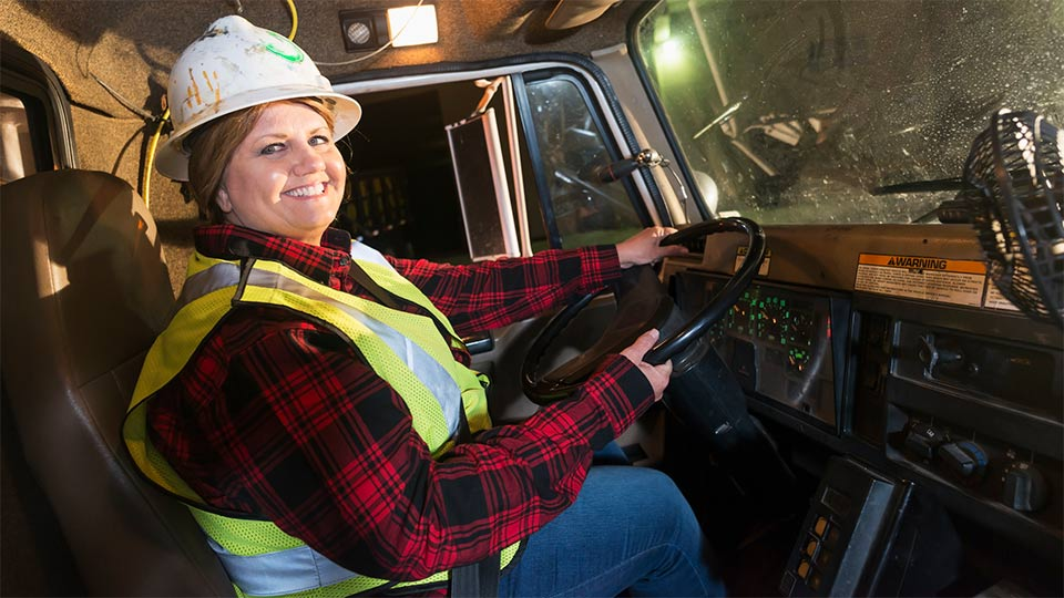 Woman wearing a vest and hardhat driving a truck