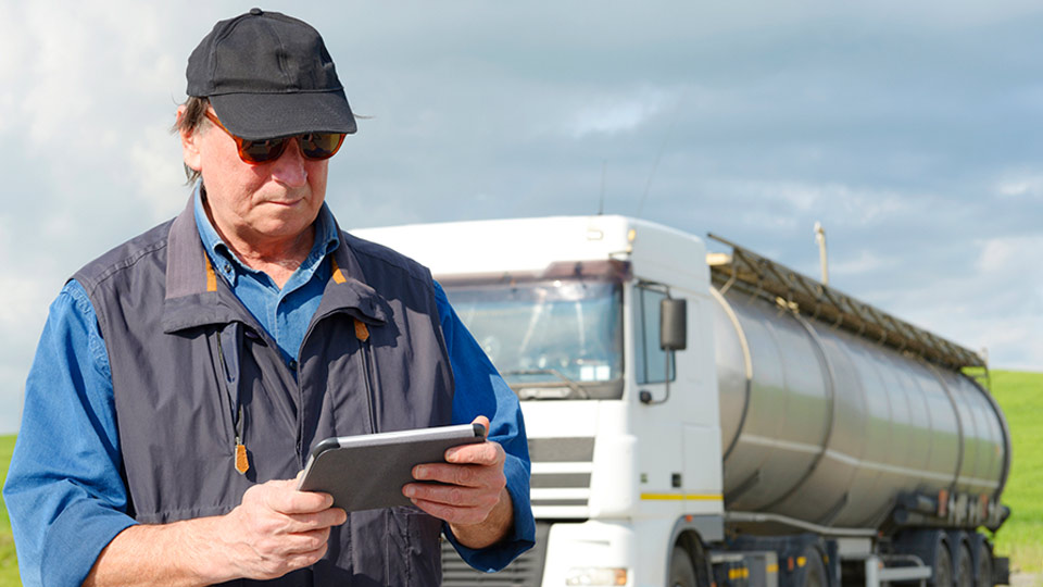 Man in a vest using an electronic logging device outside in front of a truck