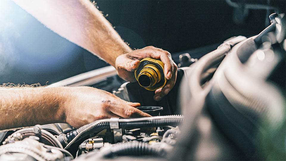 Hands working on a vehicle engine