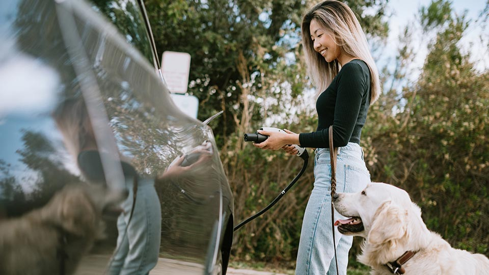 Young woman charging her electric vehicle outside.