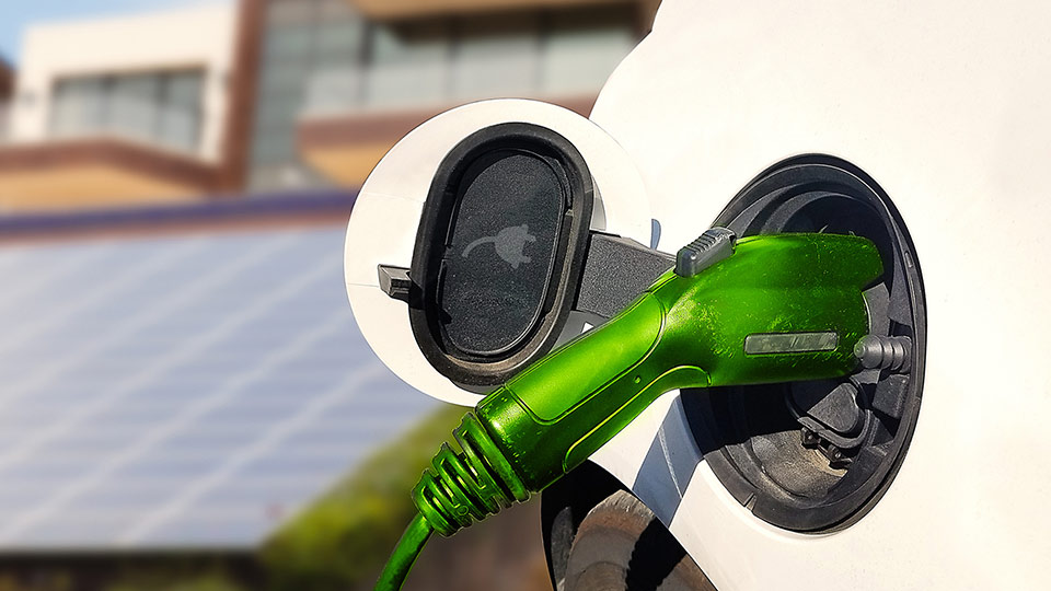 White electric vehicle charging outdoors in front of a solar panel