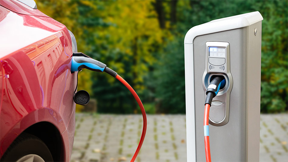 Red electric vehicle charging outside