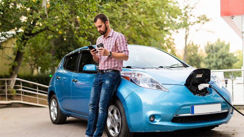 Man in front of a charging electric vehicle.
