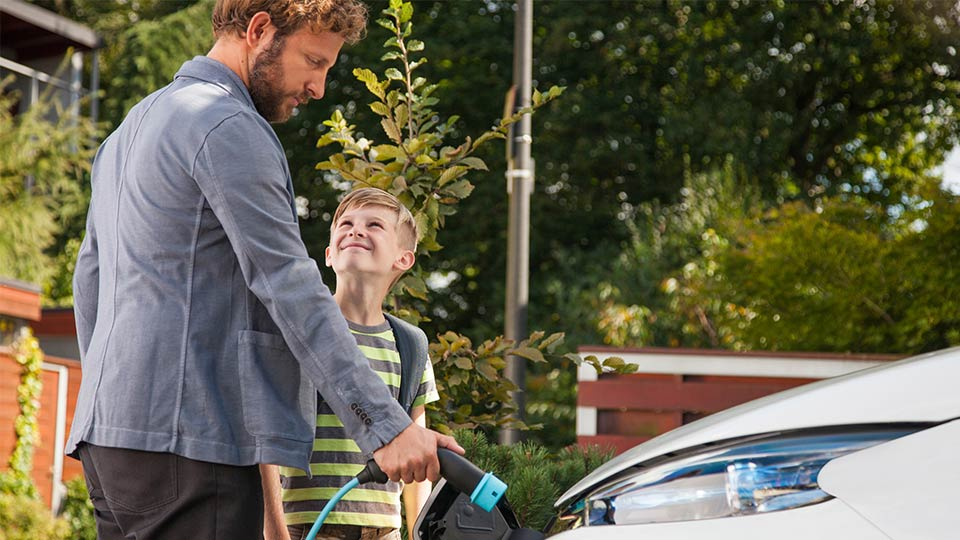 Father and son charging an electric vehicle outside