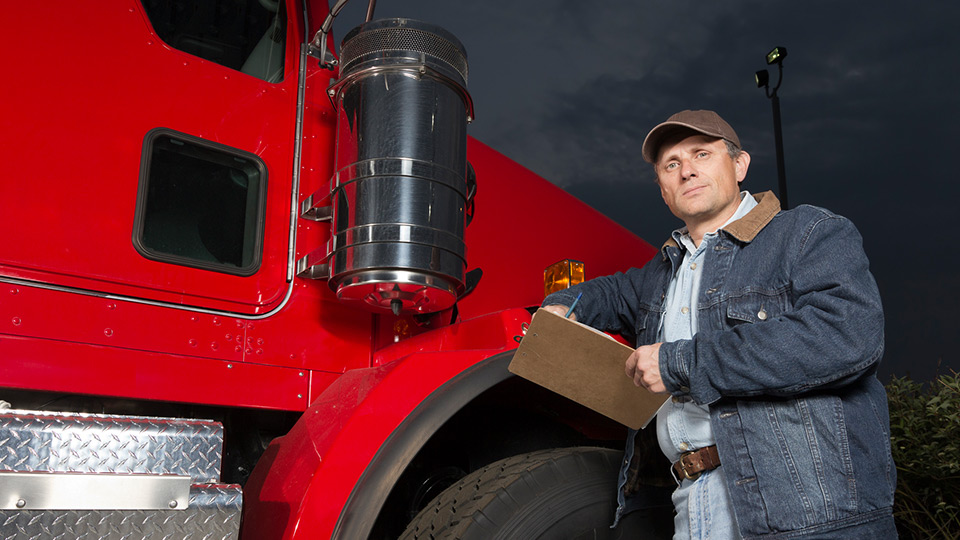 Red truck with a man holding a clipboard in front of it calculating hours of service.