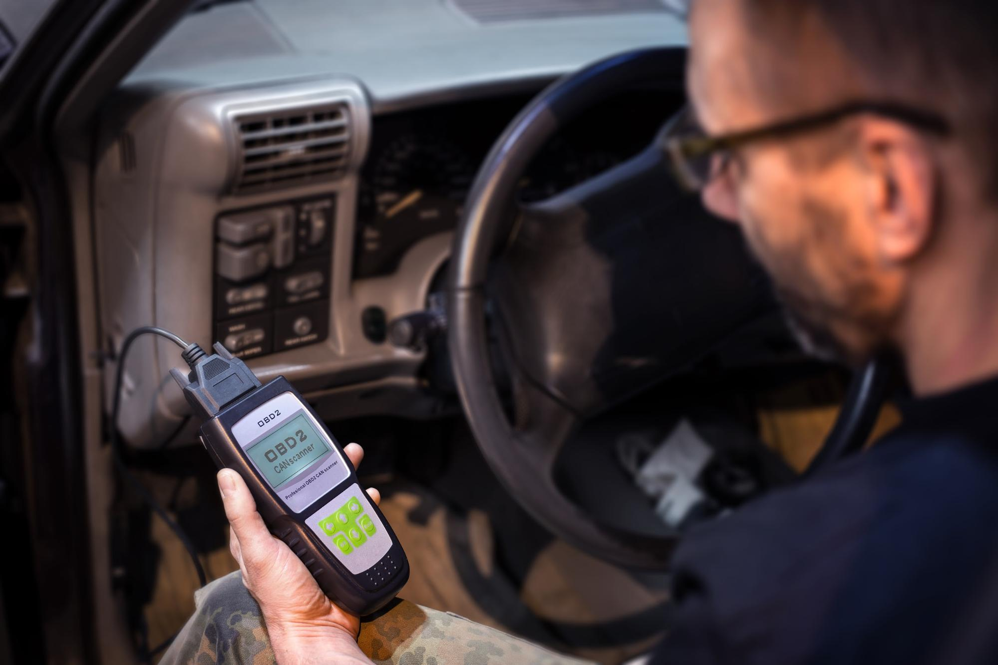 A man extracting vehicle data from an OBDII port