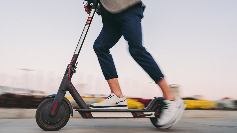 Person on a scooter representing micromobility.