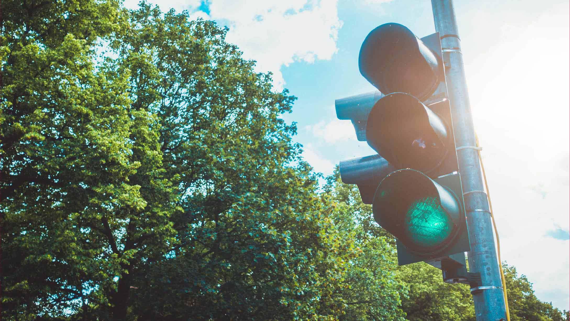 semaforo con luce verde e paesaggio attorno