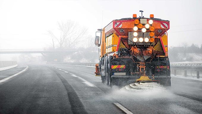 Orangefarbener Schneepflug beim Schneepflügen