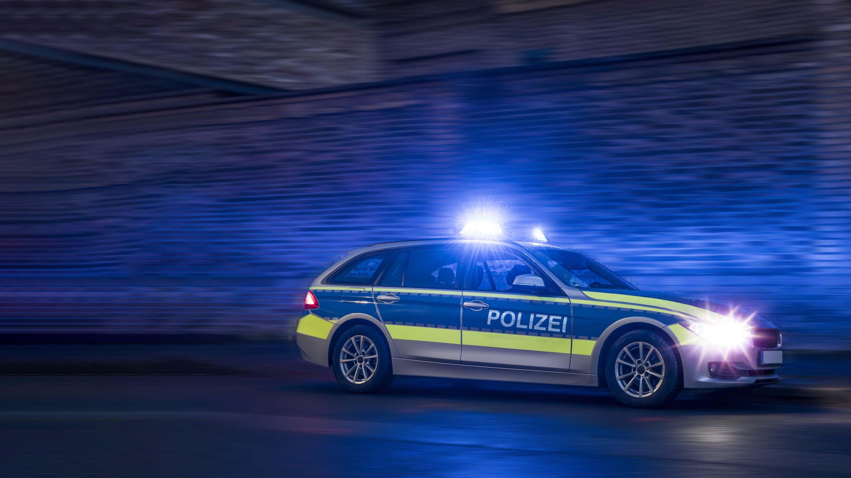 Heck eines Polizeifahrzeugs mit roten Lichtern im Hintergrund