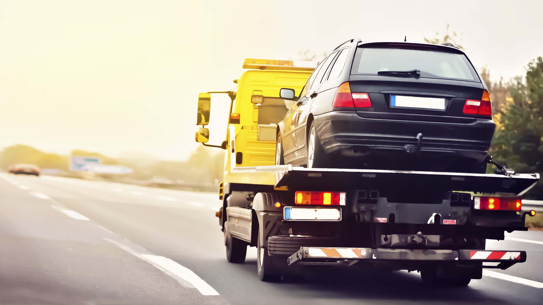 Ein Abschleppwagen fährt mit einem aufgeladenem Fahrzeug eine Straße entlang.